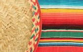 Traditional Mexican fiesta poncho rug in bright colors with sombrero — Stock Photo