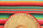 Fiesta poncho rug in bright colours with sombrero background with copy space — Stock Photo