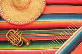 Fiesta poncho rug in bright colours with sombrero background with copy space — 图库照片