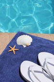 Poolside holiday vacation scenic swimming pool summer shell towel flip flops thongs — Stock Photo