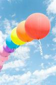 řetězec barevné balónky modré obloze mezi mraky — Stock fotografie
