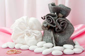Wedding rings and favors on elegant fabric — Stock Photo