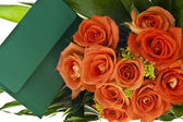 Bouquet of orange roses and ticket — Stock Photo