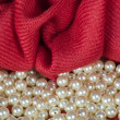Pearls  on a colored background fabric — Stock Photo