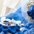 Stock Photo: Blue roses and wedding rings