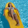 Girl relaxing in the pool on a floating mattress — Stock Photo