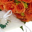 Stock Photo: Necklace and orange roses