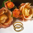 Stock Photo: Wedding rings, roses and letter