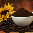 Cup with coffee powder and coffee beans scattered — Stock Photo