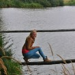 Young girl on the wooden board over a pond — Stock Photo