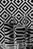 Glasses with water and geometrical ornaments on background — Stockfoto