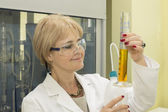 Woman in laboratory measuring cylinder — Stock Photo