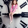 Little girl sits on a huge clockwise — Stock Photo