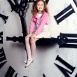 Little girl sits on a huge clockwise — Stok fotoğraf