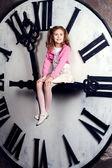 Dziewczynka siedzi na ogromną zegara — Zdjęcie stockowe