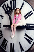 Little girl sits on a huge clockwise — Stock fotografie