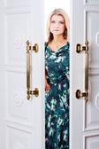 Ung kvinna kommer ut genom dörren — Stockfoto