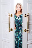 Young woman comes out of the door — Stockfoto