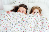 Mother and daughter look out from under the covers — Stock Photo