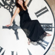 Young woman  sits on a huge clockwise — Stockfoto