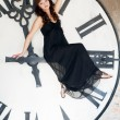 Young woman  sits on a huge clockwise — Lizenzfreies Foto