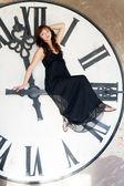 Mladá žena sedí na obrovské ve směru hodinových ručiček — Stock fotografie