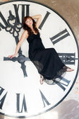 Young woman sits on a huge clockwise — Photo