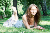 Beautiful smiling girl lying on the grass — Stock Photo