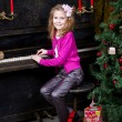Stock Photo: Happy little girl playing the piano