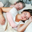 Young adult couple sleeping on the bed in bedroom   — Stock Photo