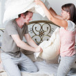Couple fighting together with pillows in bed — Stock Photo