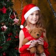 Cute little girl in a red dress near a Christmas tree — Stock Photo #35840413