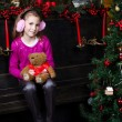Little girl sitting near the a Christmas tree — Stock Photo