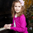 Happy little girl playing the piano — Stock Photo