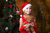 Cute little girl in a red dress near a Christmas tree — Stock Photo