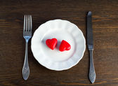 Two marzipan red hearts on a plate — Stock Photo