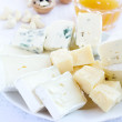 Different varieties of cheese with honey and nuts — Stock Photo