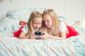 Zwei süße Mädchen auf dem Bett liegend — Stockfoto
