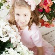Portrait of little cute girl with flowers — Stock Photo