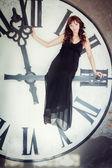 Młoda kobieta siada na ogromny zegara — Zdjęcie stockowe