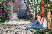 Little girl sitting in the flowered garden  — Stock Photo