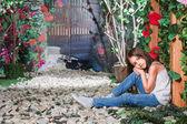 Little girl sitting in the flowered garden  — Stock Photo