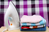 LoinclothPile of colorful clothes and electric iron on loincloth background — Stock Photo