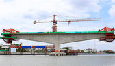 Construction crane at the bridge over the river — Stok fotoğraf