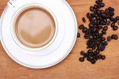 与咖啡的咖啡豆。木背景 — 图库照片