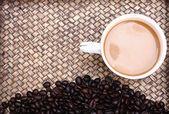 Grains de café avec du café. fond de bambou — Photo
