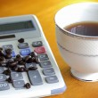 Cup of coffee and coffee beans on the calculator — Zdjęcie stockowe