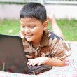 Boy playing laptop. Happily. — Stock Photo