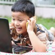The boys are playing a laptop and talking on the phone. Happily. — Stock Photo #34119477