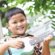 Stock Photo: Boy playing the ukulele fun.